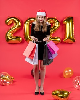 Widok z przodu młoda dama w czarnej sukience trzymająca balony torby na zakupy na czerwono