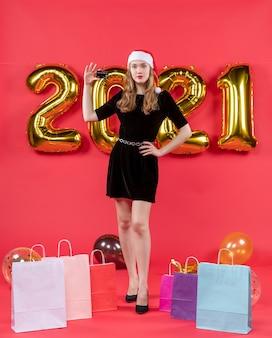 Widok z przodu młoda dama w czarnej sukience trzymająca torby na karty na balonach podłogowych na czerwono