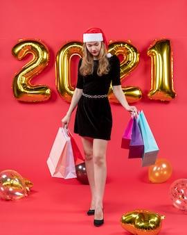 Widok z przodu młoda dama w czarnej sukience trzymająca torby na zakupy patrząca na balony podłogowe na czerwono