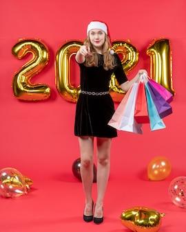Widok z przodu młoda dama w czarnej sukience trzymająca torby na zakupy, wskazując na balony aparatu na czerwono