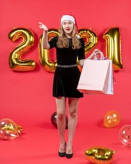 Widok z przodu młoda dama w czarnej sukience trzymająca torby na zakupy wzywająca kogoś balony na czerwono