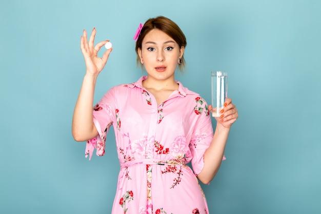Widok z przodu młoda dama w kwiat zaprojektował różową sukienkę trzymając pigułkę i szklankę wody na niebiesko