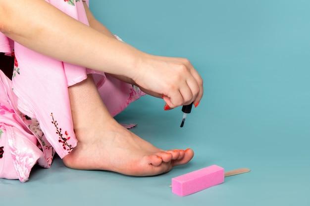 Widok z przodu młoda dama w kwiatku zaprojektowała różową sukienkę malując paznokcie na niebiesko