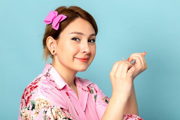 Widok z przodu młoda dama w kwiatku zaprojektowała różową sukienkę pracującą z paznokciami na niebiesko