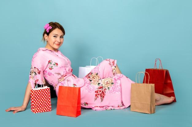 Widok z przodu młoda dama w kwiatowej różowej sukience siedzi i pozuje z uśmiechem i pakietami zakupów na niebiesko