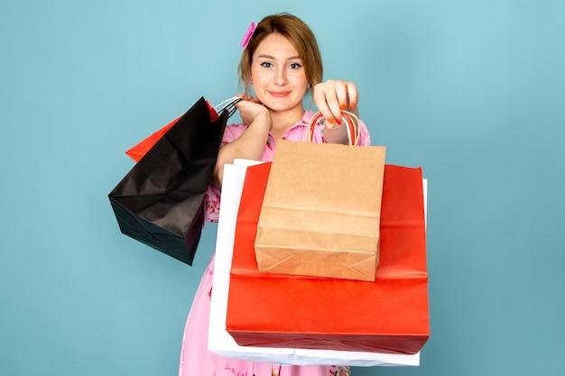Widok z przodu młoda dama w kwiatowej sukni zaprojektował różową sukienkę trzymając pakiety zakupów i uśmiechając się na niebiesko