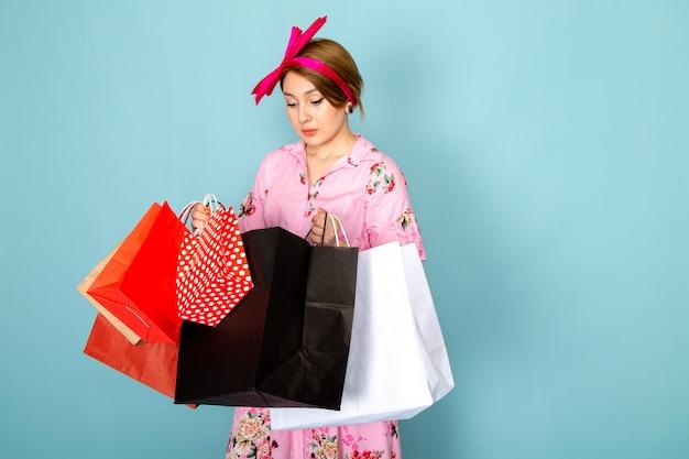 Widok z przodu młoda dama w kwiatowej sukni zaprojektował różową sukienkę trzymając pakiety zakupów na niebiesko