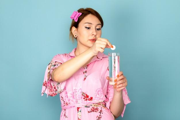 Widok z przodu młoda dama w kwiatowej sukni zaprojektował różową sukienkę wkładając pigułkę do szklanki wody na niebiesko