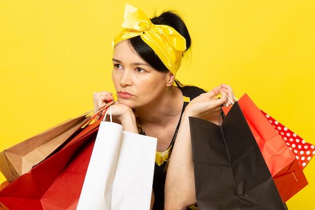 Widok z przodu młoda dama w żółto-czarnej kwiatowej sukni z żółtym bandażem na głowie myśli trzymającej paczki z zakupami na żółtym