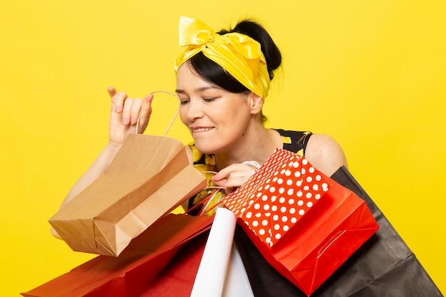 Widok z przodu młoda dama w żółto-czarnej kwiatowej sukni zaprojektowanej z żółtym bandażem na głowie pozuje trzymając paczki z zakupami na żółtym