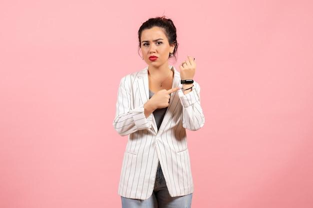 Widok z przodu młoda dama z białą kurtką wskazującą jej nadgarstek na różowym tle dama emocje moda kobieta kolor uczucie