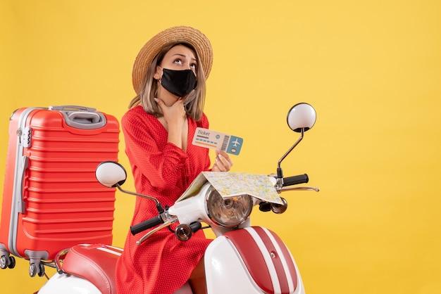 Widok z przodu młoda dama z czarną maską na motorowerze trzymająca bilet patrząc w górę