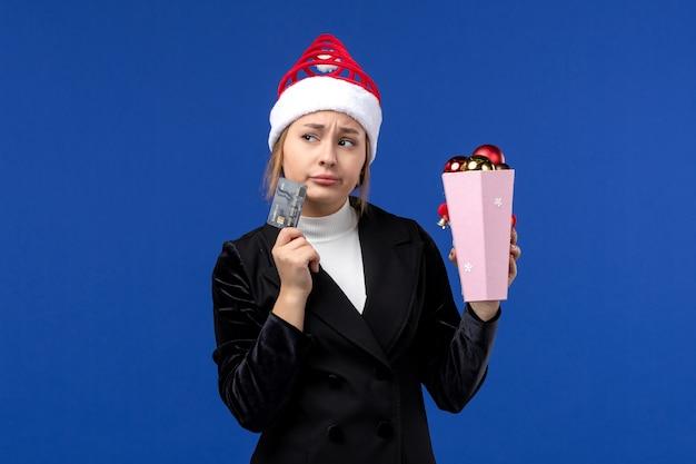Widok z przodu młoda dama z zabawkami drzewnymi i kartą bankową na niebieskiej ścianie nowy rok emocje wakacje