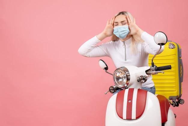 Widok z przodu młoda dama z zamkniętymi oczami na motorowerze z żółtą walizką, trzymając głowę