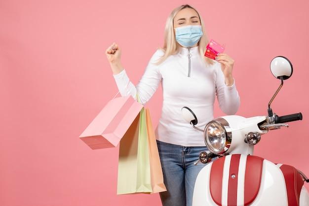 Widok z przodu młoda dama z zamkniętymi oczami trzymająca karty i torby na zakupy w pobliżu motoroweru