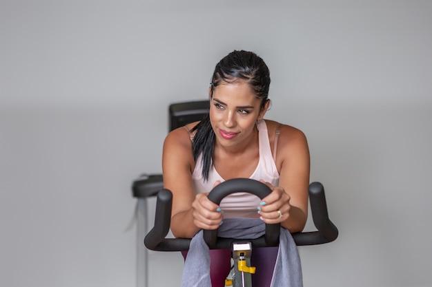 Widok z przodu młoda dorosła kobieta uśmiechając się, odwracając wzrok w odzieży sportowej, ćwicząc na rowerze w siłowni.