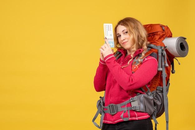Widok z przodu młoda dumna podróżująca dziewczyna w masce medycznej trzymając bilet