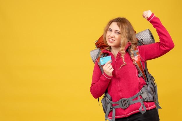 Widok z przodu młoda dumna podróżująca dziewczyna w masce medycznej trzymając kartę bankową