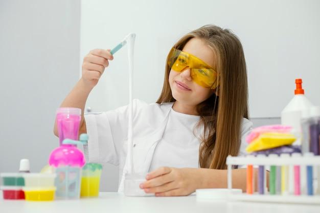 Widok z przodu młoda dziewczyna naukowiec eksperymentujący ze szlamem