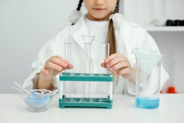 Widok z przodu młoda dziewczyna naukowiec z probówki