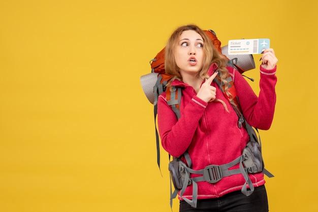 Widok z przodu młoda dziewczyna podróżująca zaskoczona w masce medycznej, trzymając i wskazując bilet