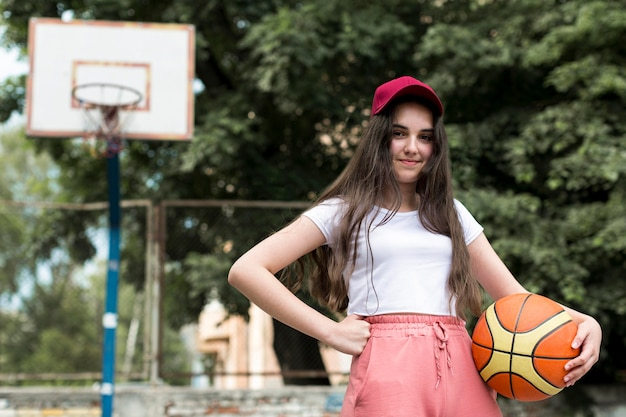 Widok z przodu młoda dziewczyna trzyma koszykówkę