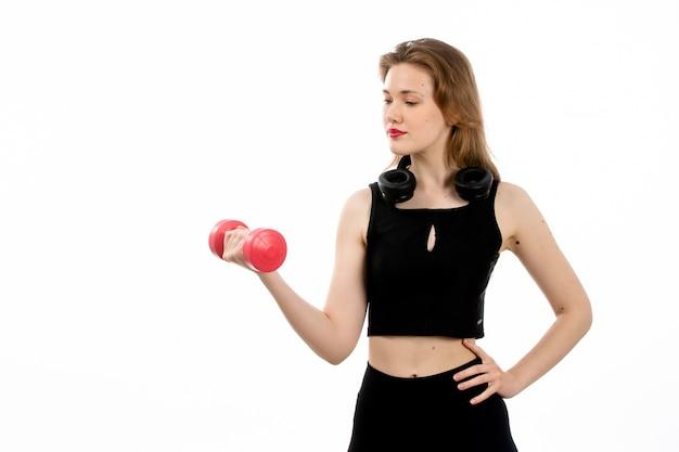 Widok z przodu młoda dziewczyna w czarnej koszuli i czarnych spodniach uprawia sport z czerwonymi hantlami na białym