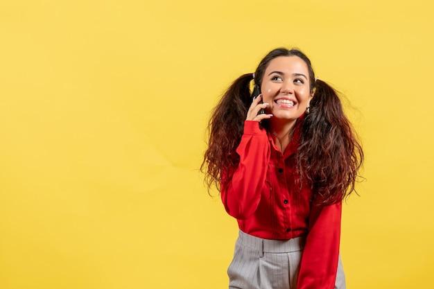 Widok z przodu młoda dziewczyna w czerwonej bluzce z ładnymi włosami rozmawia przez telefon na żółtym tle kolor dzieciak dziewczyna dziecko młodzież niewinność