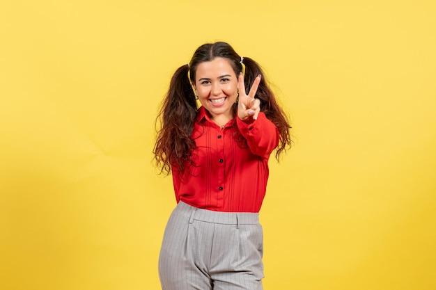 Widok z przodu młoda dziewczyna w czerwonej bluzce ze szczęśliwą pozowanie twarzą na żółtym tle kolor niewinność dziecko młodzież dziecko dziewczyna