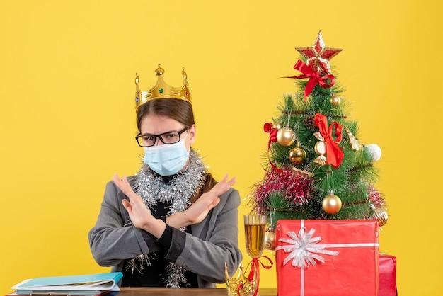 Widok z przodu młoda dziewczyna z maską medyczną krzyżując ręce boże narodzenie drzewo i prezenty koktajl