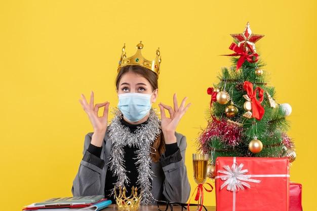Widok z przodu młoda dziewczyna z maską medyczną noszącą koronę, dzięki czemu znak okey xmas i koktajl prezenty