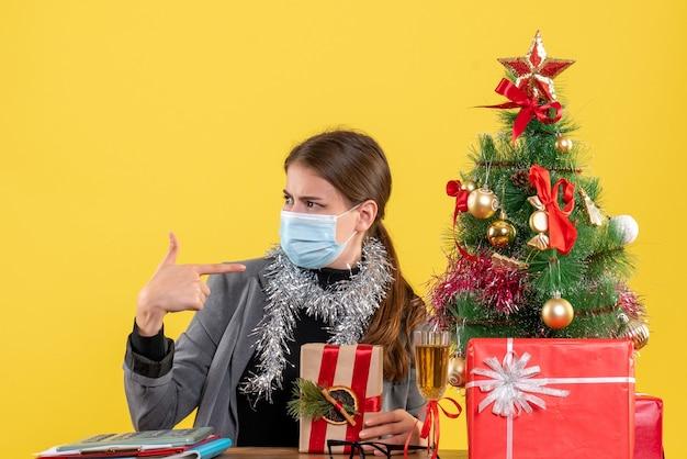 Widok z przodu młoda dziewczyna z maską medyczną patrząc na lewe drzewo xmas i koktajl prezenty
