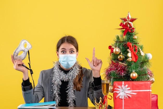 Widok z przodu młoda dziewczyna z maską medyczną siedzi przy biurku trzymając maskę maskaradową boże narodzenie drzewo i koktajl prezenty