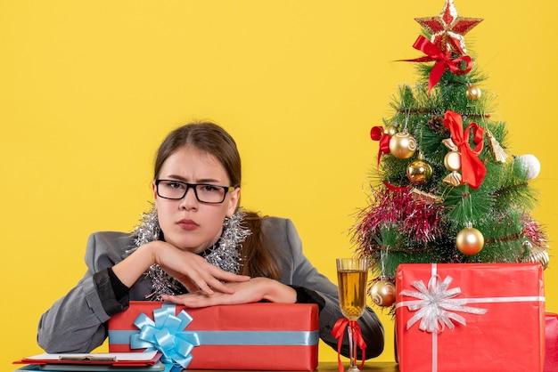 Widok z przodu młoda dziewczyna z okularami siedzi przy stole patrząc na kamery z wścibskimi oczami boże narodzenie drzewo i prezenty koktajl