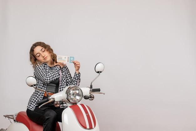Widok z przodu młoda dziewczyna z zamkniętymi oczami na motorowerze trzymająca bilet