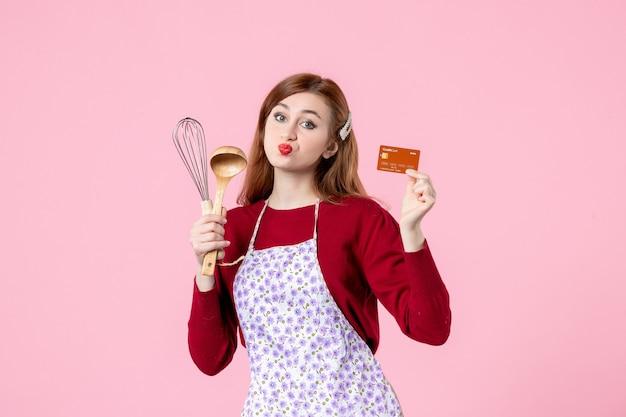 Widok z przodu młoda gospodyni domowa trzymająca trzepaczkę i kartę bankową na różowym tle kolor słodka kuchnia gotowanie kuchnia kobieta ciasto jedzenie