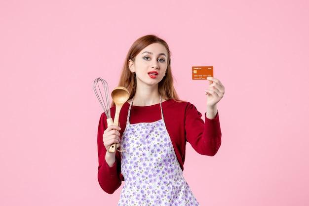 Widok z przodu młoda gospodyni domowa trzymająca trzepaczkę i kartę bankową na różowym tle kuchnia ciasto ciasto kobieta kolor zakupy gotowanie pieniądze jedzenie