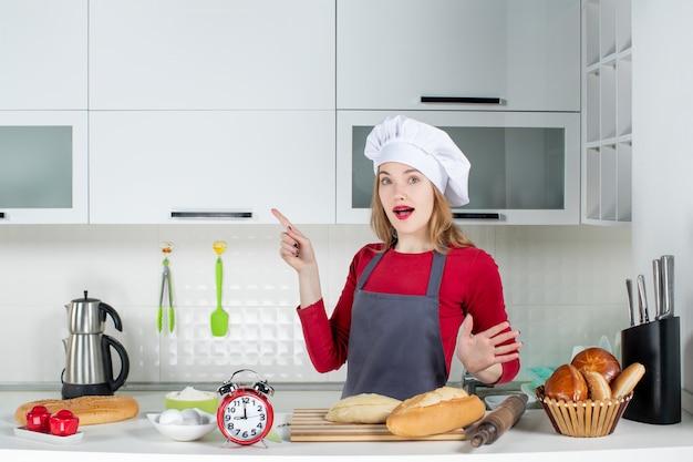 Widok z przodu młoda gospodyni domowa w kapeluszu kucharza i fartuchu w kuchni