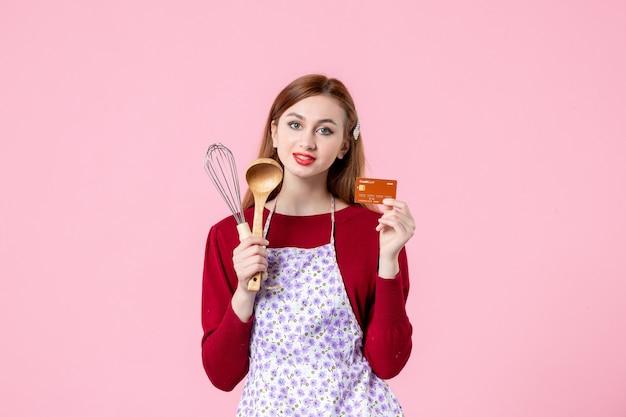 Widok z przodu młoda gospodyni trzymająca trzepaczkę i kartę bankową na różowym tle ciasto ciasto kobieta kolor zakupy gotowanie kuchnia kuchnia jedzenie