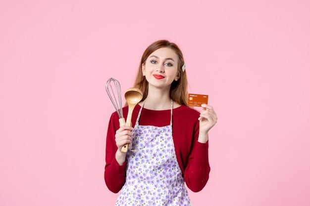 Widok z przodu młoda gospodyni trzymająca trzepaczkę i kartę bankową na różowym tle ciasto ciasto kobieta kolor zakupy gotowanie kuchnia pieniądze kuchnia jedzenie