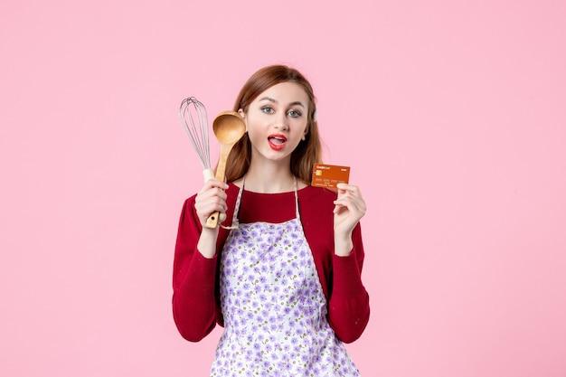 Widok z przodu młoda gospodyni trzymająca trzepaczkę i kartę bankową na różowym tle ciasto ciasto kobieta kolor zakupy gotowanie kuchnia pieniądze kuchnia