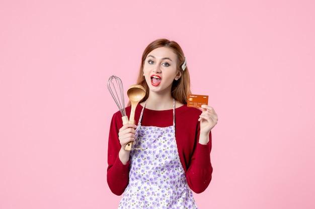 Widok z przodu młoda gospodyni trzymająca trzepaczkę i kartę bankową na różowym tle ciasto ciasto kobieta kolor zakupy gotowanie pieniądze kuchnia jedzenie