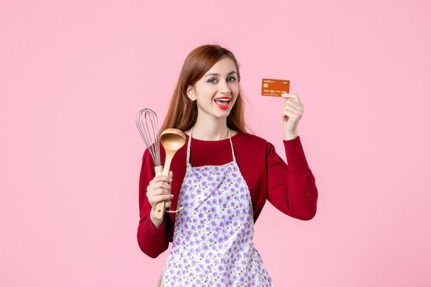 Widok z przodu młoda gospodyni trzymająca trzepaczkę i kartę bankową na różowym tle ciasto słodkie jedzenie kuchnia gotowanie kuchnia kobieta kolor ciasta