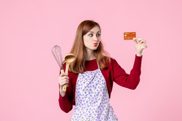 Widok z przodu młoda gospodyni trzymająca trzepaczkę i kartę bankową na różowym tle ciasto słodkie jedzenie kuchnia gotowanie kuchnia kobieta kolorowy tort
