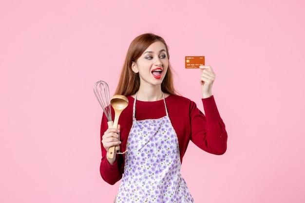 Widok z przodu młoda gospodyni trzymająca trzepaczkę i kartę bankową na różowym tle ciasto słodkie jedzenie kuchnia gotowanie kuchnia kolor ciasto