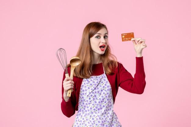 Widok z przodu młoda gospodyni trzymająca trzepaczkę i kartę bankową na różowym tle ciasto słodkie jedzenie kuchnia kuchnia kobieta kolor ciasta