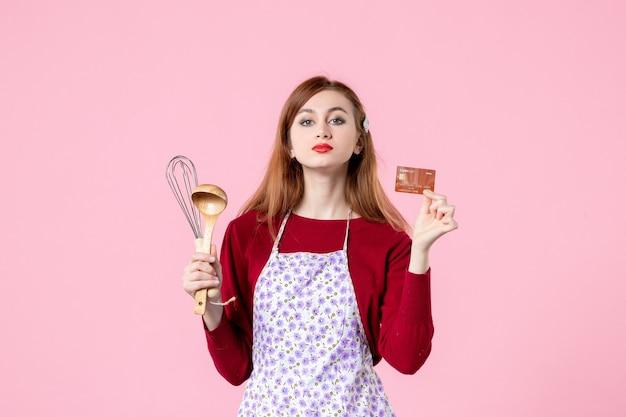 Widok z przodu młoda gospodyni trzymająca trzepaczkę i kartę bankową na różowym tle kobieta kolor ciasto kuchnia zakupy gotowanie ciasto jedzenie pieniądze