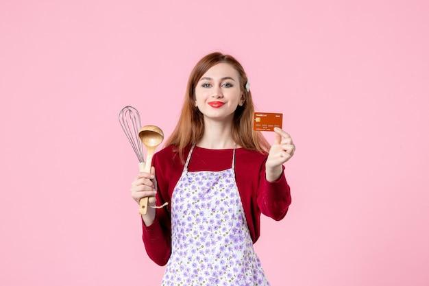 Widok z przodu młoda gospodyni trzymająca trzepaczkę i kartę bankową na różowym tle kobieta kolor ciasto kuchnia zakupy gotowanie kuchnia ciasto pieniądze