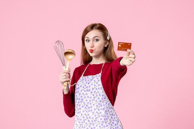 Widok z przodu młoda gospodyni trzymająca trzepaczkę i kartę bankową na różowym tle kolor ciasta słodka kuchnia gotowanie kuchnia kobieta ciasto