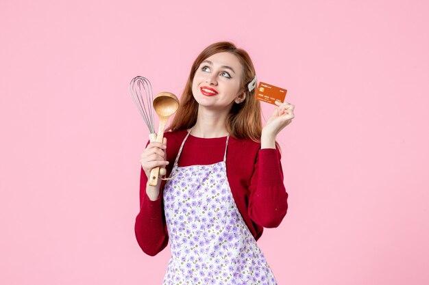 Widok z przodu młoda gospodyni trzymająca trzepaczkę i kartę bankową na różowym tle kolor ciasto kuchnia zakupy gotowanie kuchnia kobieta ciasto pieniądze